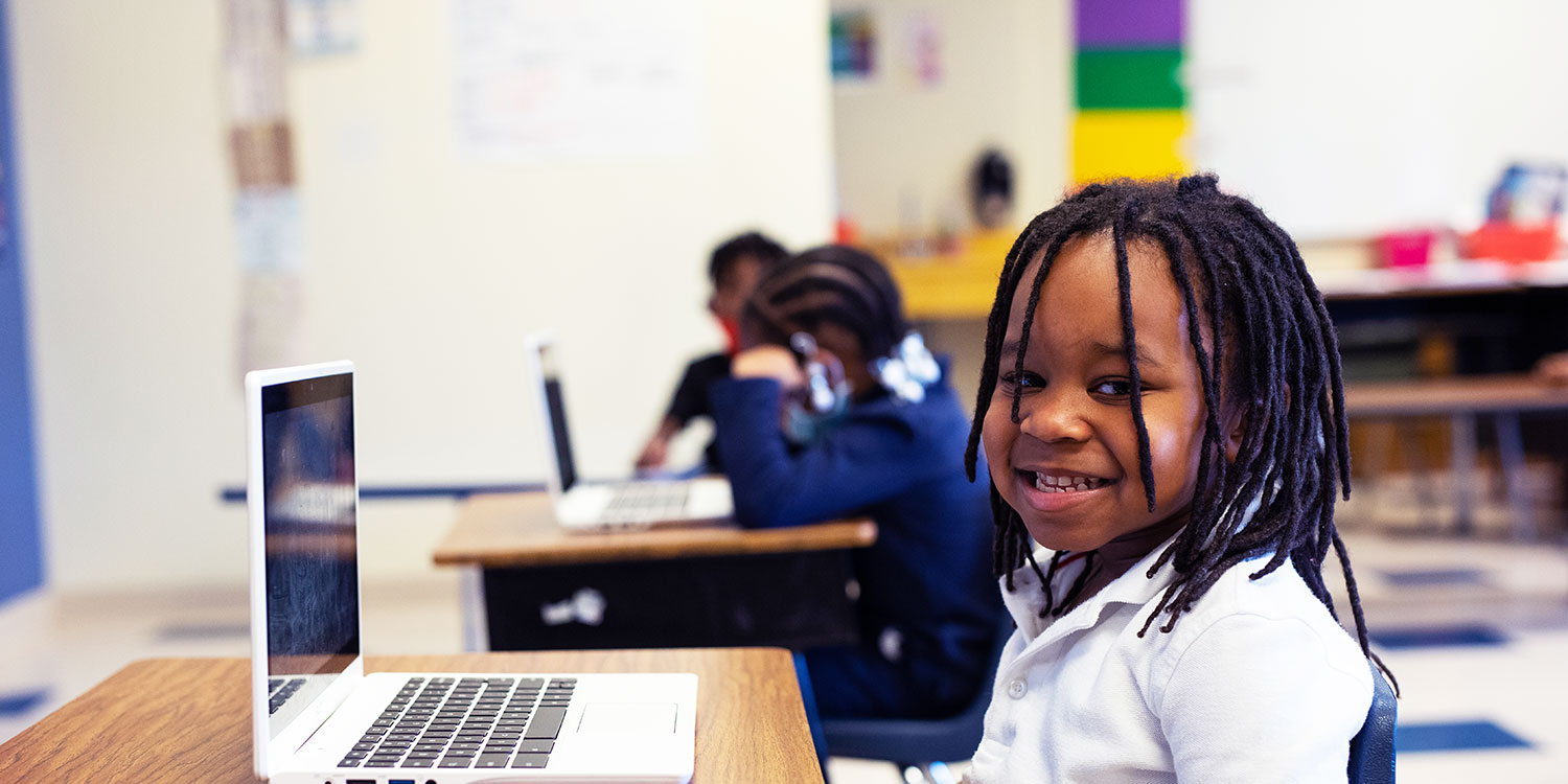 Student smiling sitting at desk with laptop.