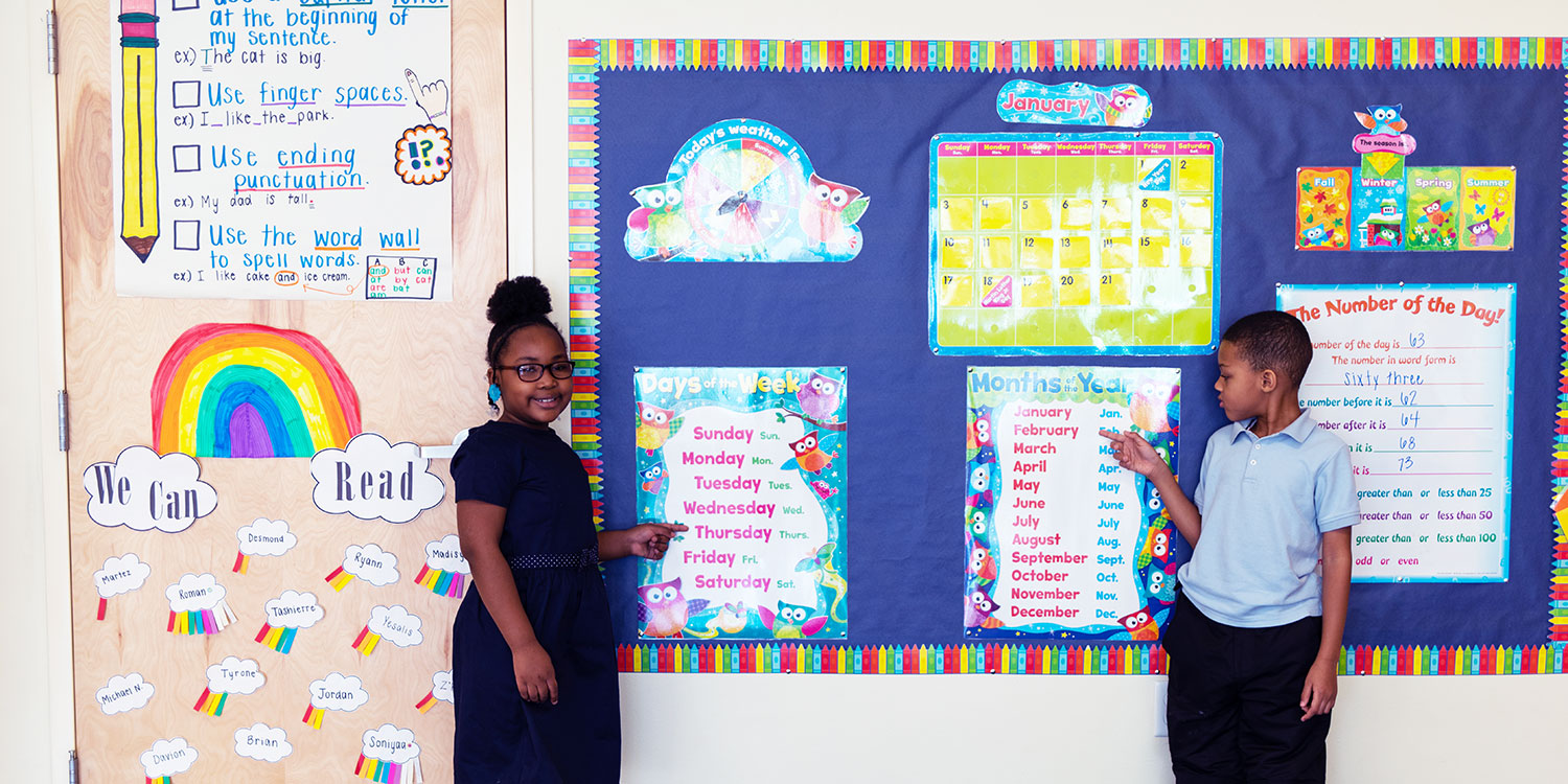Elementary students standing and pointing to posters in classroom.