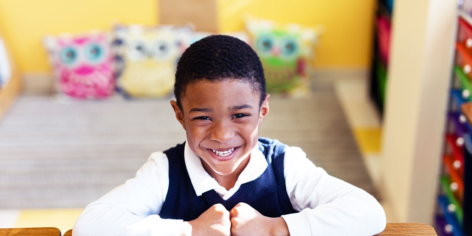 Smiling student sitting at desk in classroom.