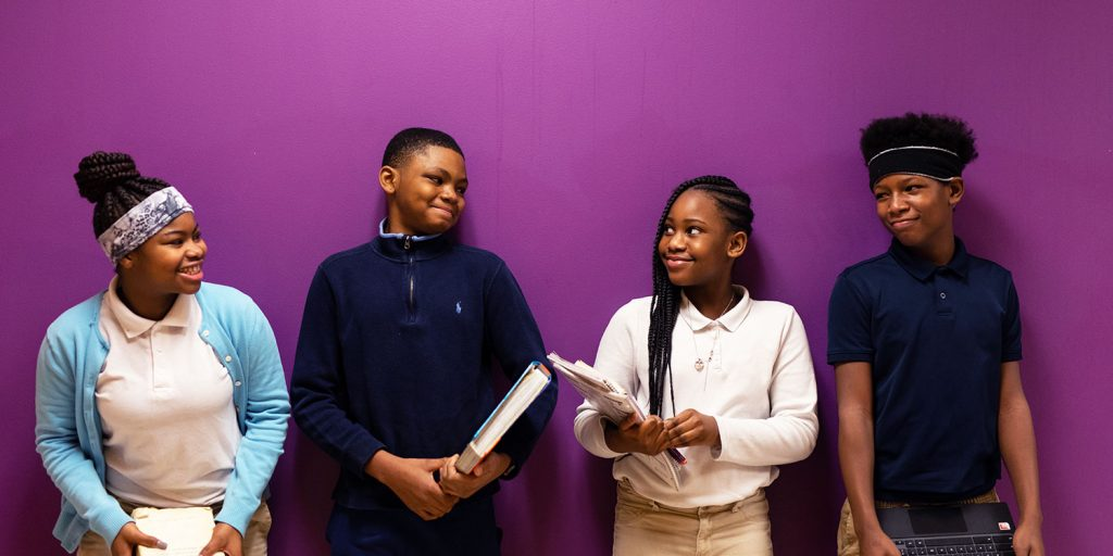 Smiling students standing next to each other against a purple wall.