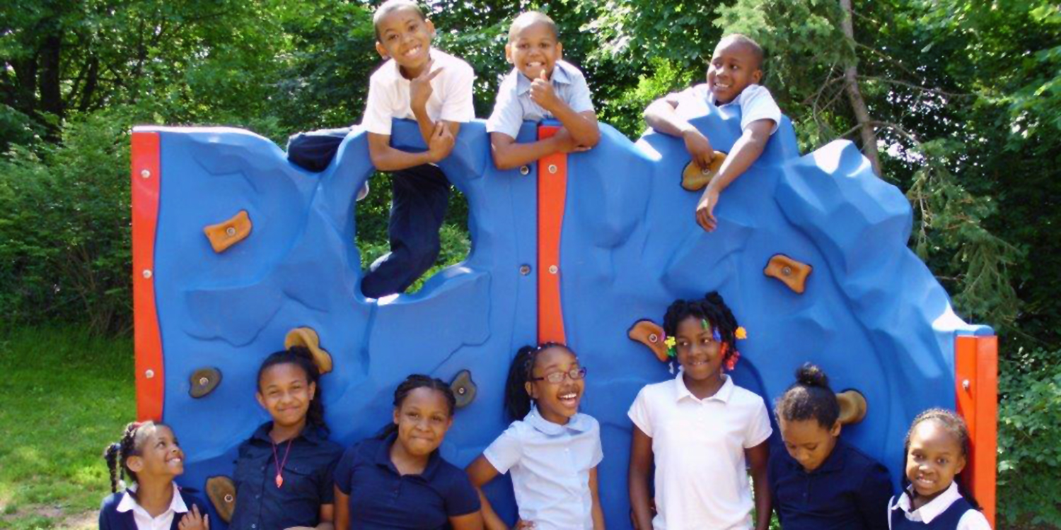 Elementary students standing outside by rock climbing playground structure.
